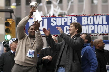 NEW YORK - FEBRUARY 05:  New York Giants defensive end Michael Strahan (L) passes the Vince Lombardi trophy to team mate Eli Manning  during the New York Giants Superbowl XLII victory parade February 5, 2008 in New York City.  (Photo by Chris McGrath/Gett