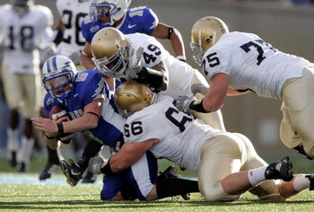 AIR FORCE ACADEMY, CO - NOVEMBER 11:  Defensive linemen Derek Landri #66, Chris Frome #75 and linebacker Tiryan Smith #49 of the Notre Dame Fighting Irish bring down quarterback Shaun Carney #5 of the Air Force Falcons in the second quarter on November 11