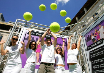 LONDON, ENGLAND - JUNE 23:  WTA staff throw balls in the air to celebrate an interactive mobile tennis game on a giant plasma screen during which passers by can challenge No 7 Vera Zvonareva in the WTA live digital gaming event at Covent Garden during Wim