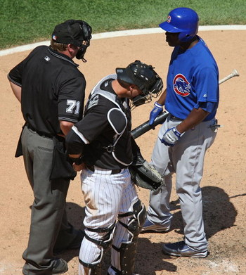 CHICAGO - JUNE 28:  Milton Brandley #21 of the Chicago Cubs asks for the count from home plate umpire Brain Runge #71 as A.J. Pierzynski #12 of the Chicago White Sox listens on June 28, 2009 at U.S. Cellular Field in Chicago, Illinois. The White Sox defea