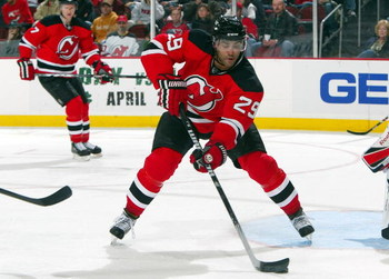 NEWARK, NJ - APRIL 11:  Johnny Oduya #29 of the New Jersey Devils skates against the Carolina Hurricanes at the Prudential Center on April 11, 2009 in Newark, New Jersey. The Devils defeated the Hurricanes 3-2.  (Photo by Jim McIsaac/Getty Images)