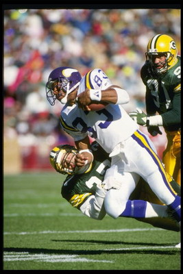28 Oct 1990: MINNESOTA VIKINGS WIDE RECEIVER STEVE JORDAN #83 CARRIES THE FOOTBALL AND RUNS OVER AN UNIDENTIFIED GREEN BAY PACKERS DEFENDER, DURING THE VIKINGS 24-10 LOSS AT Milwaukee County Stadium in Milwaukee, Wisconsin.