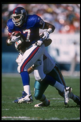 8 Dec 1996:  Tight end Howard Cross of the New York Giants (left) runs with the ball as Miami Dolphins linebacker Zach Thomas attempts to tackle him during a game at Pro Player Stadium in Miami, Florida.  The Giants won the game, 17-7. Mandatory Credit: A
