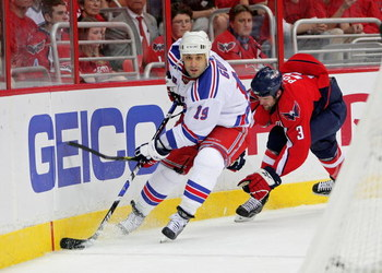 WASHINGTON - APRIL 28: Scott Gomez #19 of the New York Rangers skates the puck past Tom Poti #3   of the Washington Capitals during Game Seven of the Eastern Conference Quarterfinal Round of the 2009 Stanley Cup Playoffs on April 28, 2009 at the Verizon C