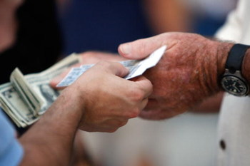 ST PETERSBURG, FL - OCTOBER 22:  A fan holds tickets and another holds money before the Philadelphia Phillies take on the Tampa Bay Rays during game one of the 2008 MLB World Series on October 22, 2008 at Tropicana Field in St. Petersburg, Florida.  (Phot