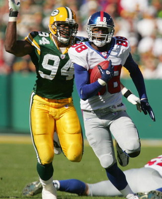 GREEN BAY, WI - OCTOBER 3:  Wide receiver Ike Hilliard #88 of the New York Giants evades defensive end Kabeer Gbaja-Biamila #94 of the Green Bay Packers during the game on October 3, 2004 at Lambeau Field in Green Bay, Wisconsin.  The Giants won 14-7.  (P