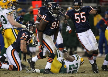 CHICAGO - DECEMBER 22: Tommie Harris #91 and Lance Briggs #55 of the Chicago Bears celebrate a tackle for a loss against Ryan Grant #25 of the Green Bay Packers on December 22, 2008 at Soldier Field in Chicago, Illinois. The Bears defeated the Packers 20-
