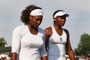 WIMBLEDON, ENGLAND - JUNE 25:  Venus Williams of USA (R) and Serena Williams of USA (L) look on during the women's doubles first round match against Virginie Razzano of France and Aravane Rezai of France on Day Four of the Wimbledon Lawn Tennis Championsh