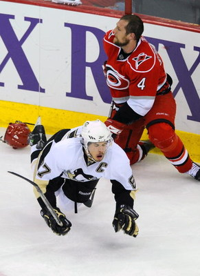RALEIGH, NC - MAY 26:  Dennis Seidenberg #4 of the Carolina Hurricanes trips Sidney Crosby #87 of the Pittsburgh Penguins during Game Four of the Eastern Conference Championship Round of the 2009 Stanley Cup Playoffs at RBC Center May 26, 2009 in Raleigh,