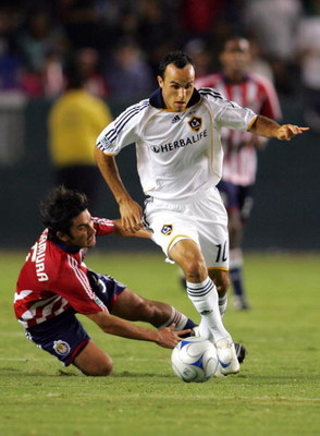 CARSON, CA - AUGUST 14:  Landon Donovan #10 of the Los Angeles Galaxy dribbles the ball past a falling Paulo Nagamura #5 of CD Chivas USA in the second half of their MLS match at the Home Depot Center on August 14, 2008 in Carson, California. The Galaxy a