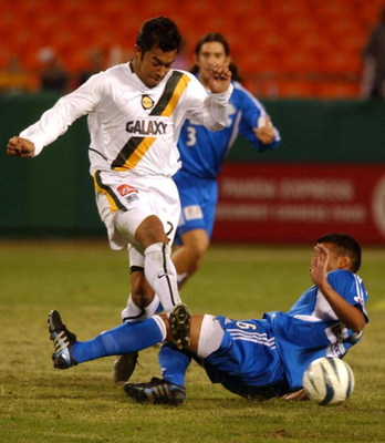 KANSAS CITY, MO - NOVEMBER 5:  Forward Carlos Ruiz #20 of the Los Angeles Galaxy runs over defender Jose Burciaga Jr. #6 of the Kansas City Wizards during the Major League Soccer Western Conference final on November 5, 2004 at Arrowhead Stadium in Kansas