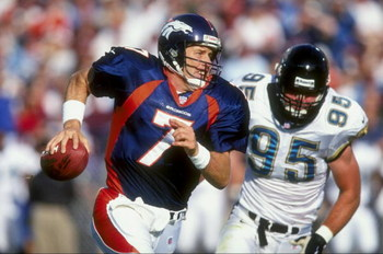 25 Oct 1998: Quarterback John Elway #7 of the Denver Broncos runs as he avoids being sacked by Bryce Paup #95 of the Jacksonville Jaguars at Mile High Stadium in Denver, Colorado. The Broncos defeated the Jaguars 37- 24.