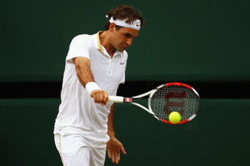 WIMBLEDON, ENGLAND - JULY 03:  Roger Federer of Switzerland plays a backhand during the men's singles semi final match against Tommy Haas of Germany on Day Eleven of the Wimbledon Lawn Tennis Championships at the All England Lawn Tennis and Croquet Club o