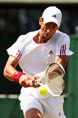 WIMBLEDON, ENGLAND - JULY 01:  Novak Djokovic of Serbia plays backhand during the men's singles quarter final match against Tommy Haas of Germany on Day Nine of the Wimbledon Lawn Tennis Championships at the All England Lawn Tennis and Croquet Club on Jul