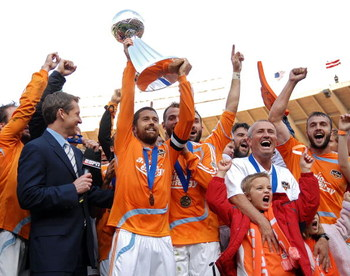 WASHINGTON - NOVEMBER 18:  Wade Barrett #24 of the Houston Dynamo holds up the trophy in celebration with his team after defeating the New England Revolution by a score of 2-1 to win the 2007 Major League Soccer Cup at RFK Stadium on November 18, 2007 in
