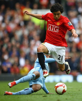 MANCHESTER, ENGLAND - MAY 10:  Rafael of Manchester United hurdles the tackle of Robinho of Manchester City during the Barclays Premier League match between Manchester United and Manchester City at Old Trafford on May 10, 2009 in Manchester, England.  (Ph
