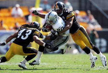 PITTSBURGH - SEPTEMBER 12:  Justin Fargas #20 of the Oakland Raiders runs with the ball while tackled by  Troy Polamalu #43 and Larry Foote #50 of the Pittsburgh Steelers on September 12, 2004 at Heinz Field in Pittsburgh, Pennsylvania. The Steelers won 2