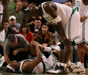 BOSTON - DECEMBER 15:  Paul Pierce #34 of the Boston Celtics is looked after by Ed Lecerte and teammate Kevin Garnett #5 after Pierce injured his knee late in the fourth quarter against the Utah Jazz on December 15, 2008 at TD Banknorth Garden in Boston,