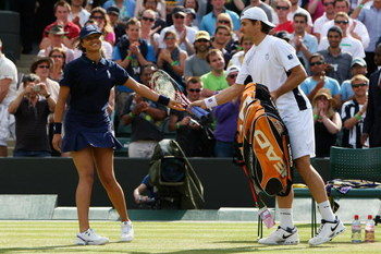 WIMBLEDON, ENGLAND - JUNE 24:  Tommy Haas of Germany passes a racquet to a ball girl as Michael Llodra of France is treated during the men's singles second round match on Day Three of the Wimbledon Lawn Tennis Championships at the All England Lawn Tennis