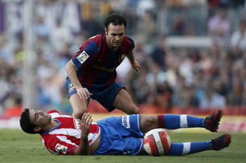 BARCELONA, SPAIN - OCTOBER 07: Andres Iniesta (R) of Barcelona challenges a fallen Jose Antonio Reyes of Atletico de Madrid during the Primera Liga match between Barcelona and Atletico de Madrid at the Camp Nou stadium on October 7, 2007 in Barcelona, Spa