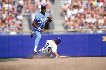 1990:  Frank White #20 of the Kansas City Royals tries to turn a double play as he throws to first base after forcing out the sliding runner at second base during a game in 1990.  (Photo by Otto Greule Jr/Getty Images)