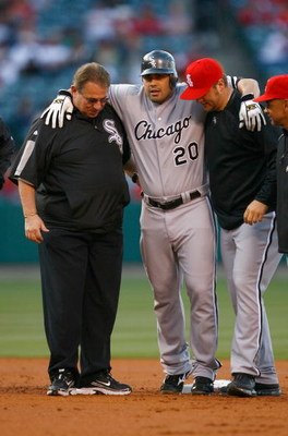 ANAHEIM, CA - MAY 25:  Carlos Quentin #20 of the Chicago White Sox is helped off the field after hitting a double and sustaining an injury in the first inning against the Los Angeles Angels of Anaheim at Angel Stadium on May 25, 2009 in Anaheim, Californi