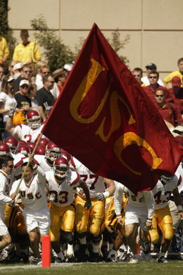 BOULDER, CO - SEPTEMBER 14:   The USC Trojan banner leads the team as they take the field during the NCAA football game against the Colorado Buffaloes at Folsom Field in Boulder, Colorado on September 14, 2002.  The University of Southern California won 4