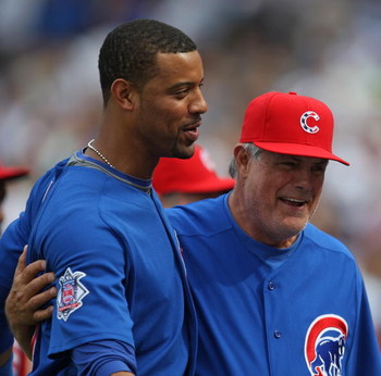 CHICAGO - JULY 03: Derrek Lee #25 and Manager Lou Piniella #41 of the Chicago Cubs celebrate a win over the Milwaukee Brewers on July 3, 2009 at Wrigley Field in Chicago, Illinois. The Cubs defeated the Brewers 2-1 in 10 innings. (Photo by Jonathan Daniel