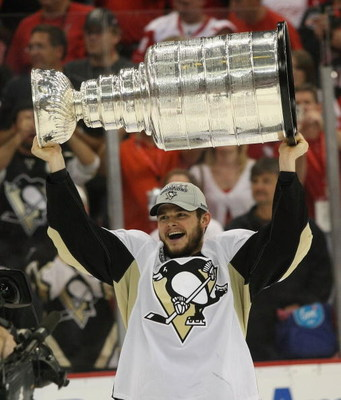 DETROIT - JUNE 12: Chris Kunitz #14 of the Pittsburgh Penguins holds the Stanley Cup following the Penguins victory over the Detroit Red Wings in Game Seven of the 2009 NHL Stanley Cup Finals at Joe Louis Arena on June 12, 2009 in Detroit, Michigan. (Phot