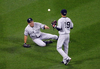 NEW YORK - JUNE 26:  Johnny Damon #18 of the New York Yankees flips the ball to teammate Ramiro Pena #19 after making a catch against the New York Mets on June 26, 2009 at Citi Field in the Flushing neighborhood of the Queens borough of New York City.  (P