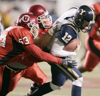 SALT LAKE CITY, UT - NOVEMBER 20: Taylor Miller #53 and Sione Pouha #90 of University of Utah sack John Beck #12 of BYU late in the fourth quarter November 20, 2004 at Rice Eccles Stadium in Salt Lake City, Utah. (Photo by George Frey/Getty Images)