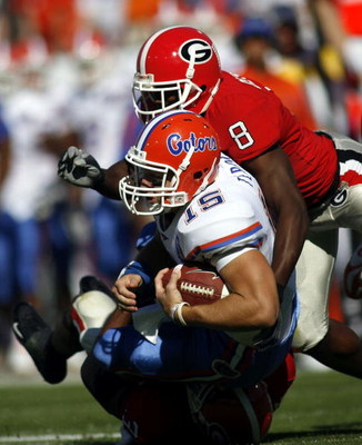 JACKSONVILLE, FL - OCTOBER 28:  Tim Tebow #15 of the University of Florida Gators is brought down by Paul Oliver #8 of the University of Georgia Bulldogs at Alltel  Stadium on October 28, 2006 in Jacksonville, Florida. Florida defeated Georgia 21-14.  (Ph