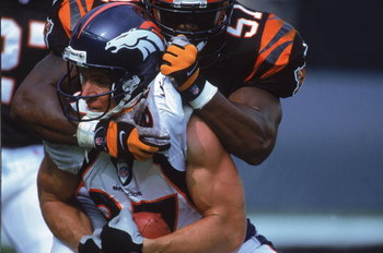 22 Oct 2000:  Ed McCaffrey #87# of the Denver Broncos gets pulled down by Takeo Spikes #51 of the Cincinnati Bengals during the game at the Paul Brown Stadium in Cincinnati, Ohio. The Bengals defeated the Broncos 31-21.Mandatory Credit: Jonathan Daniel  /