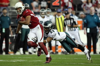 GLENDALE, AZ - JANUARY 18:  Wide receiver Larry Fitzgerald #11 of the Arizona Cardinals attempts to run by a tackle attempt by cornerback Asante Samuel #22 of the Philadelphia Eagles during the NFC championship game on January 18, 2009 at University of Ph