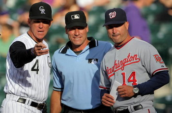 DENVER - JULY 06:  Manager Jim Tracy #4 of the Colorado Rockies reviews the ground rules with manager Manny Acta #14 of the Washington Nationals and homeplate umpire Angel Hernandez (C) prior to the game during MLB action at Coors Field on July 6, 2009 in