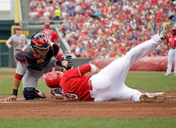 CINCINNATI - JULY 04:  Joey Votto #19 of the Cincinnati Reds is tagged out a home plate by Yadier Molina #4 of the St. Louis Cardinals at the Great American Ball Park on July 4, 2009 in Cincinnati, Ohio.  (Photo by Andy Lyons/Getty Images)