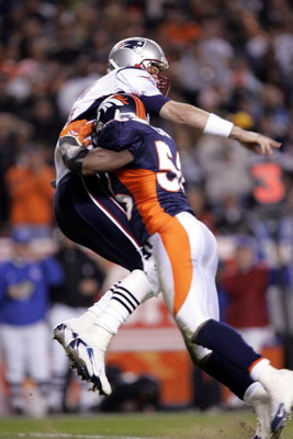 DENVER - JANUARY 14:  Quarterback Tom Brady #12 of the New England Patriots gets hit by Al Wilson #56 of the Denver Broncos during the AFC Divisional Playoff game on January 14, 2006 at Invesco Field at Mile High in Denver, Colorado.  (Photo by Brian Bahr
