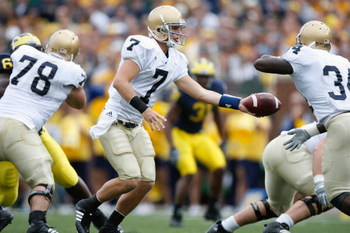 ANN ARBOR, MI - SEPTEMBER 15:  Jimmy Clausen #7 hands off to James Aldridge #34 of the Notre Dame Fighting Irish during the game against the Michigan Wolverines on September 15, 2007 at Michigan Stadium in Ann Arbor, Michigan. Michigan won 38-0. (Photo by