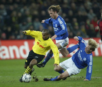 DORTMUND, GERMANY - JANUARY 30: Ewerthon of Dortmund in action against Neil Oude Kamphuis and Christain Poulsen of Schalke during the Bundsliga match between Borussia Dortmund and  FC Schalke 04 at The Westfallen Stadium on 30 January, 2004 in Dortmund, G