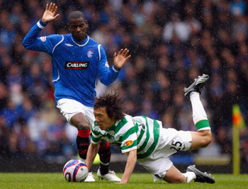 GLASGOW, SCOTLAND - MAY 09: Maurice Edu of Rangers tackles Shunsuke Nakamura of Celtic  during the Scottish Premier League match between Rangers and Celtic at Ibrox stadium on May 9, 2009 in Glasgow, Scotland.  (Photo by Jeff J Mitchell/Getty Images)
