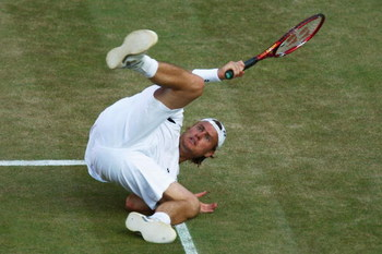 WIMBLEDON, ENGLAND - JULY 01:  Lleyton Hewitt of Australia tumbles as he plays a shot during the men's singles quarter final match against Andy Roddick of USA on Day Nine of the Wimbledon Lawn Tennis Championships at the All England Lawn Tennis and Croque