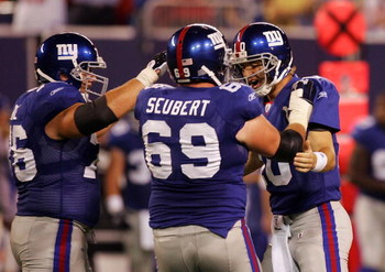 EAST RUTHERFORD, NJ - AUGUST 18:  Eli Manning #10 of the New York Giants is congratulated by teammates Rich Seubert #69 and Chris Snee #76 after he threw his second touchdown against the Cleveland Browns on August 18, 2008 at Giants Stadium in East Ruther