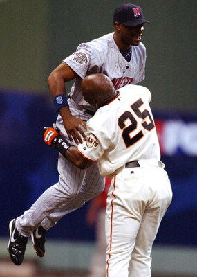 MILWAUKEE, WI - JULY 9:  Barry Bonds #25 of the National League picks up Torii Hunter #48 of the American League after Hunter robbed Bonds of a homerun at the wall for the first out in the first inning during the MLB All- Star Game on July 9, 2002 at Mill