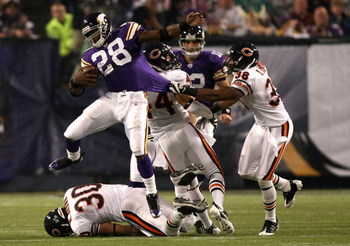 MINNEAPOLIS - NOVEMBER 30:  Adrian Peterson #28 of the Minnesota Vikings leaps over  Mike Brown #30 of the Chicago Bears as Danieal Manning #38 grabs his jersey at the Metrodome on November 30, 2008 in Minneapolis, Minnesota.  (Photo by Jonathan Ferrey/Ge