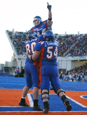 BOISE, ID - NOVEMBER 20:  Running back Jon Helmandollar #33 of Boise State is hoisted up by teammates Andy Weldon #80 and Jeff Cavender #54 after scoring a touchdown in the fourth quarter against Louisiana Tech at Bronco Stadium on November 20, 2004 in Bo