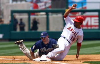 ANAHEIM, CA - JUNE 14:  Maicer Izturis #13 of the Los Angeles Angels of Anaheim is tagged out at third base by Kevin Kouzmanoff #5 of the San Diego Padres in the second inning at Angel Stadium on June 14, 2009 in Anaheim, California. The Angels defeated t