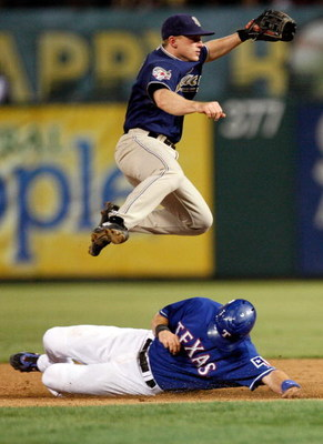 ARLINGTON, TX - JUNE 28:  Second baseman David Eckstein #3 of the San Diego Padres turns the double play over the slide by Michael Youg #10 of the Texas Rangers to end the game on June 28, 2009 at Rangers Ballpark in Arlington, Texas.  (Photo by Ronald Ma