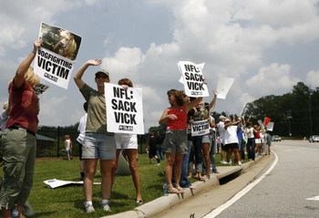 FLOWERY BRANCH, GA - JULY 26: Protesters stand outside the Atlanta Falcons team complex to show their displeasure with Michael Vick July 26, 2007 in Flowery Branch, Georgia. Falcons quarterback Michael Vick was to appear for a bond hearing and arraignment