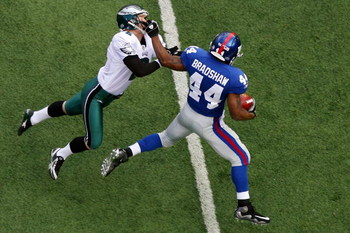 EAST RUTHERFORD, NJ - JANUARY 11:  Ahmad Bradshaw #44 of the New York Giants stiff arms kicker David Akers #2 of the Philadelphia Eagles on a return during the NFC Divisional Playoff Game on January 11, 2009 at Giants Stadium in East Rutherford, New Jerse