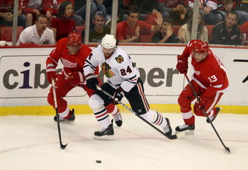 DETROIT - MAY 17:  Martin Havlat #24 of the Chicago Blackhawks attempts to control the puck against Marian Hossa (L) #81 and Pavel Datsyuk #13 of the Detroit Red Wings during the first period of Game One of the Western Conference Championship Round of the
